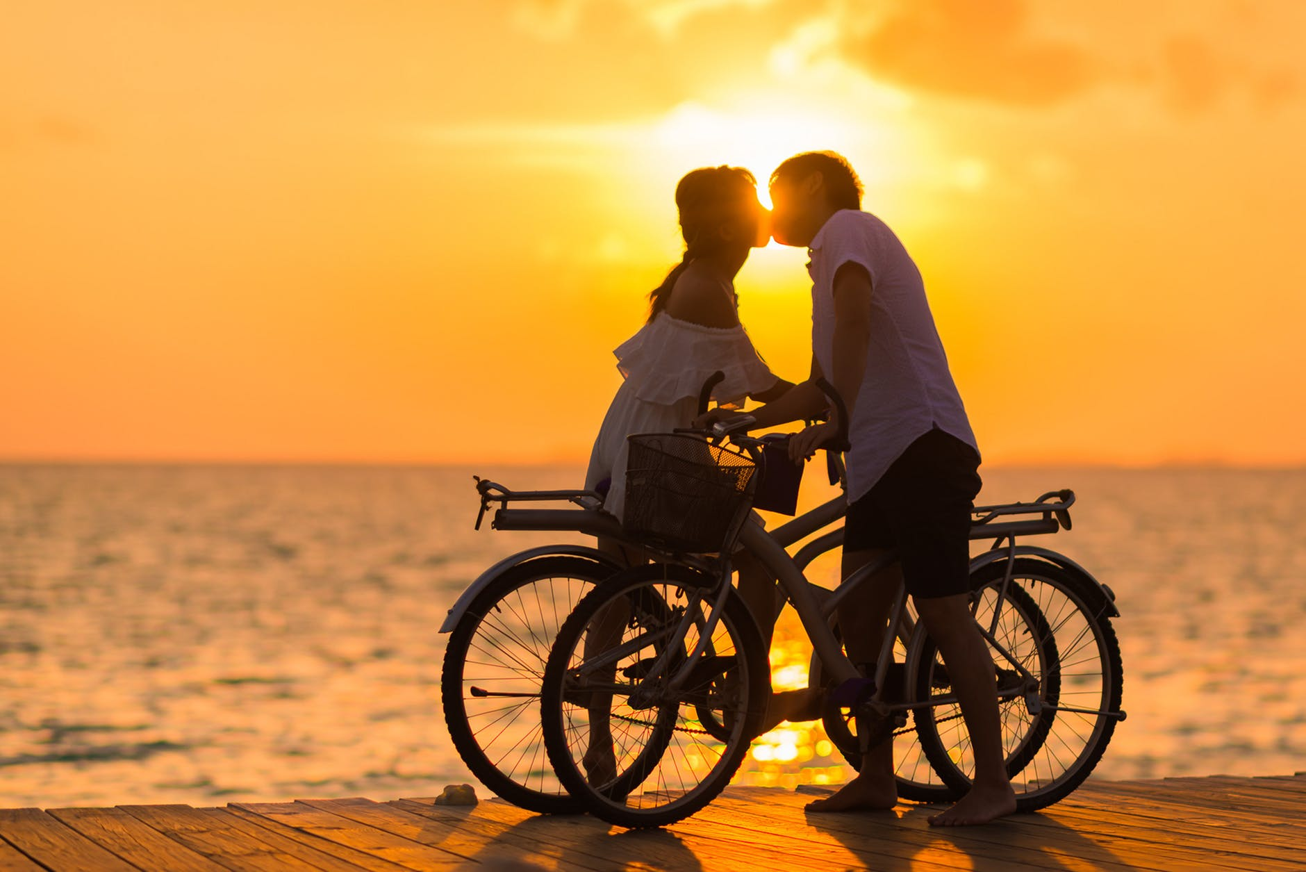 kissing on bicycle in sunset