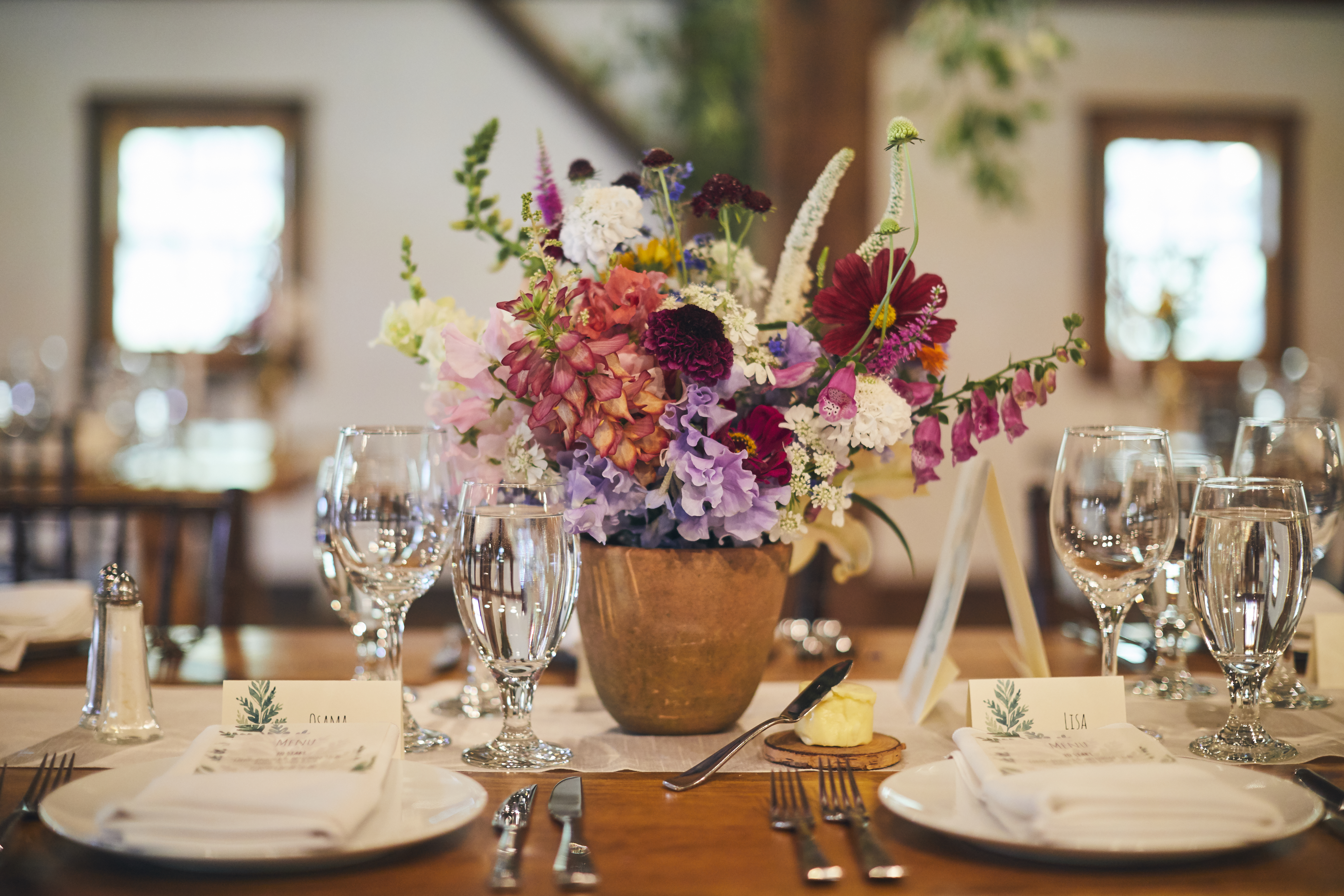 table set with water glasses and a large flower bouquet