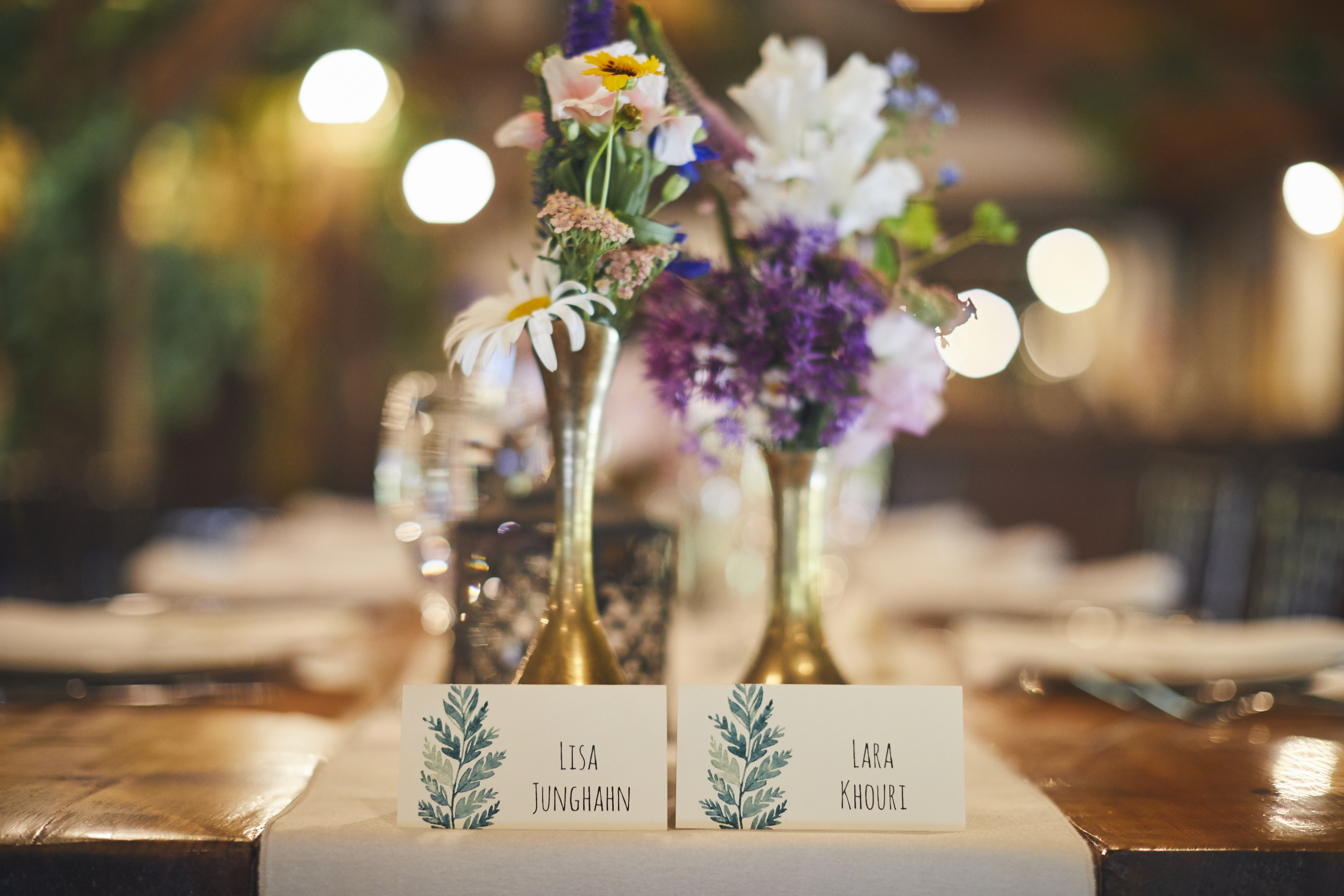Seating cards with fern design under flower vases