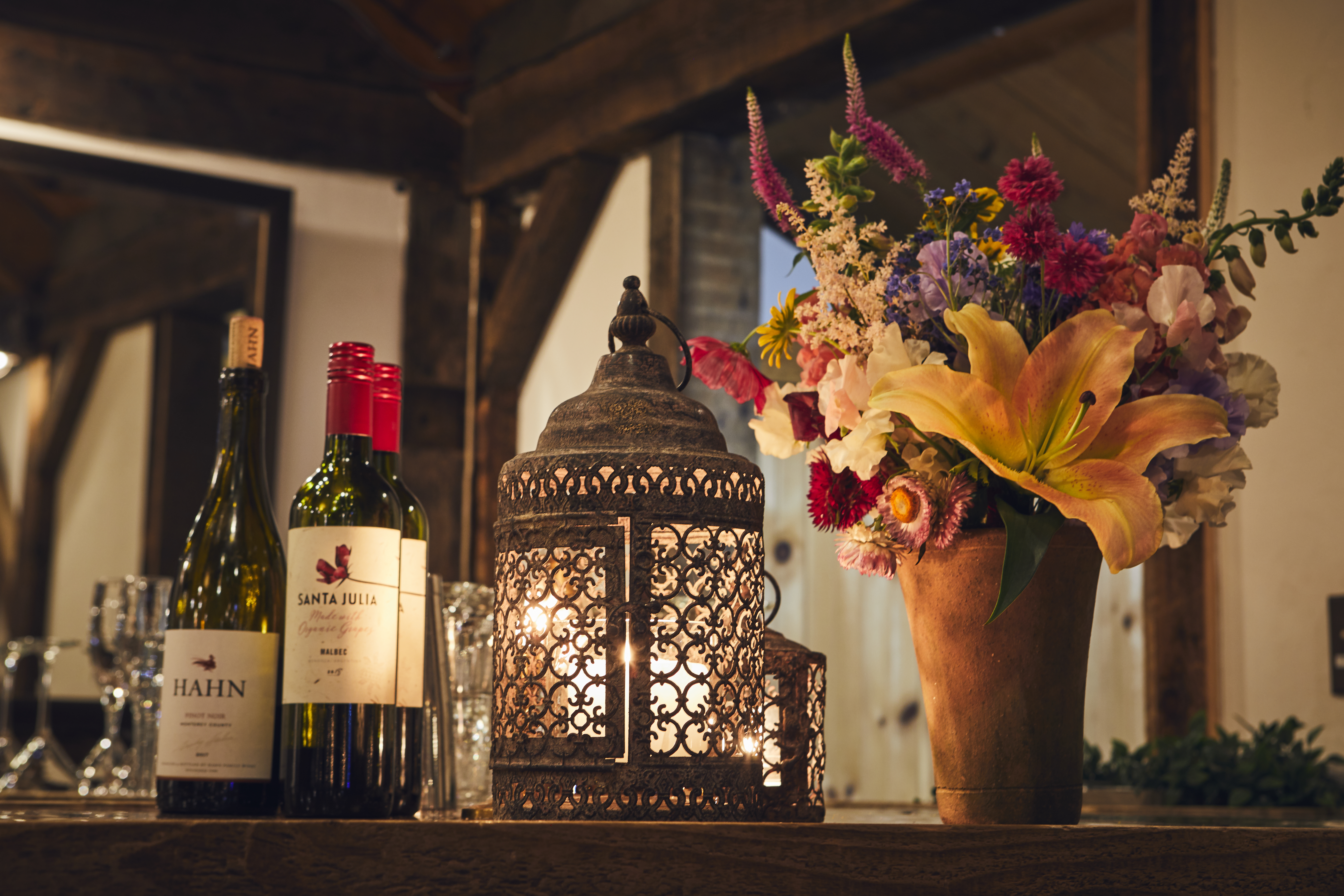 Rustic lantern with vase of flowers and wine bottles