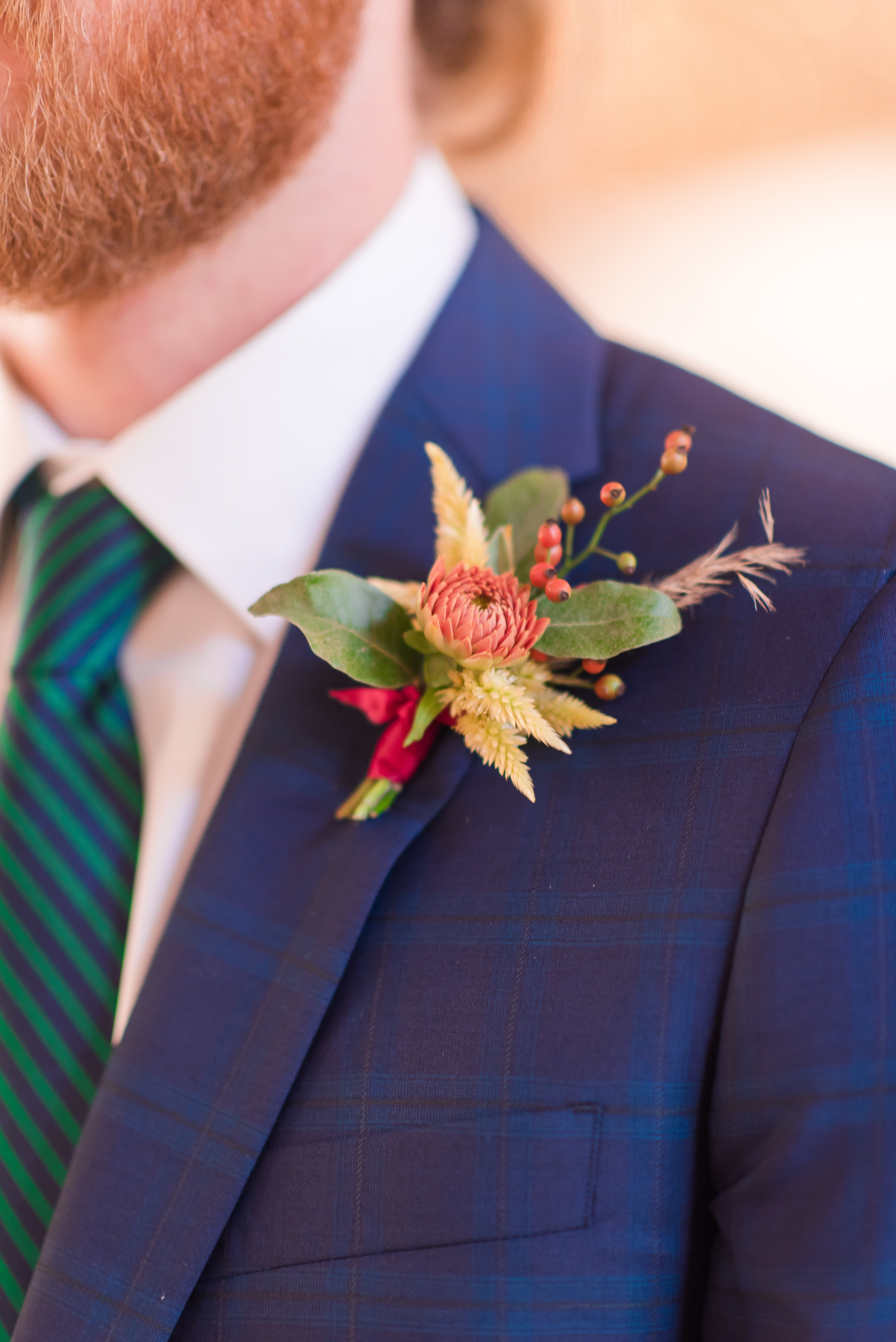 close up of boutonniere on blue suit
