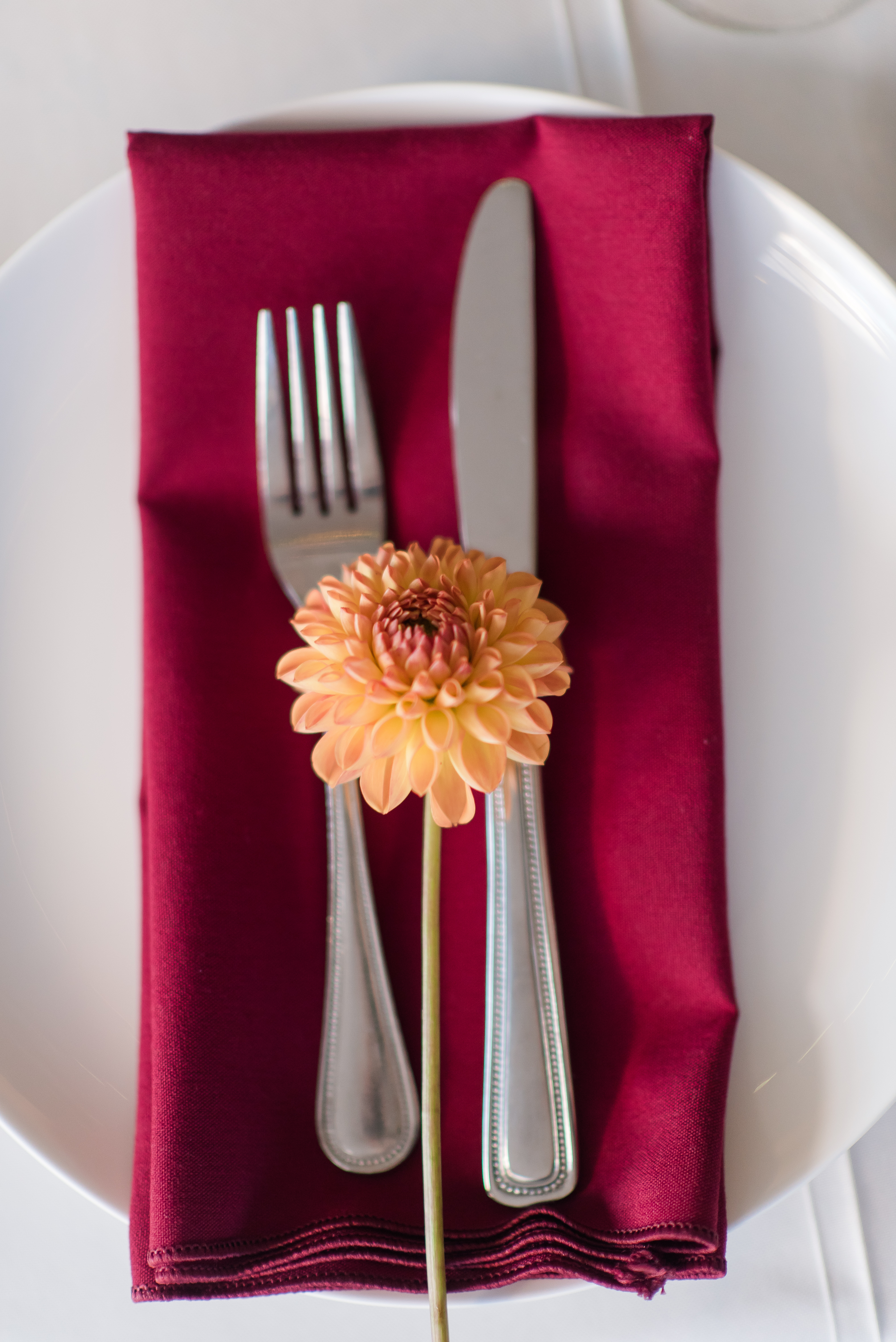 fork and knife on red napkin with flower