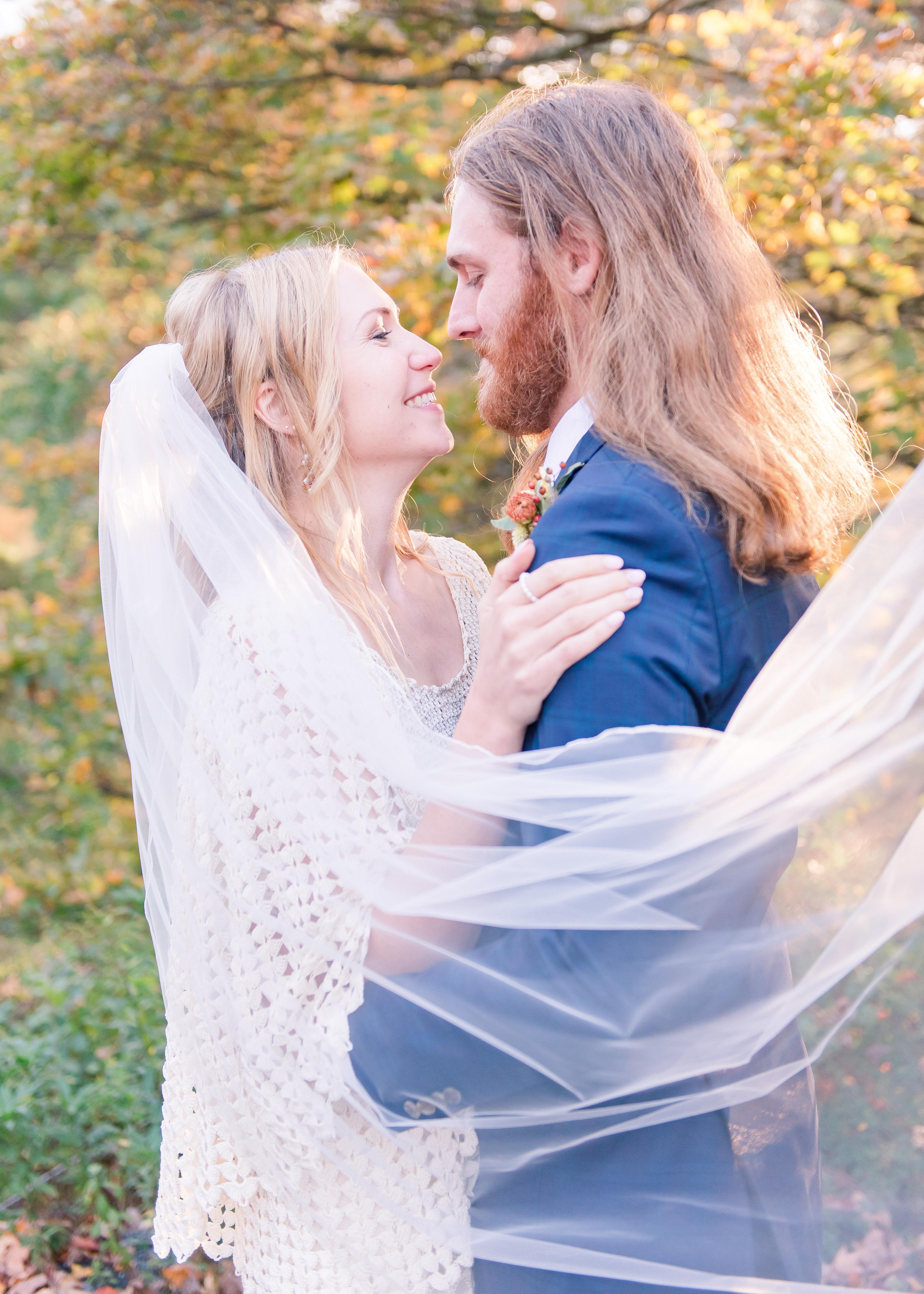 bride with veil draped around groom